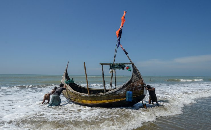 In this photograph taken on October 10, 2020, fishermen set out on a fishing boat at Sabrang beach area, a boarding point of Rohingya refugees migrating to Malaysia by boat. - Boatloads of Rohingya landing across Southeast Asia are victims of complex human trafficking networks run by a dizzying web of players, from crime bosses and corrupt cops to poor fishermen, rickshaw drivers and even Rohingya themselves. AFP