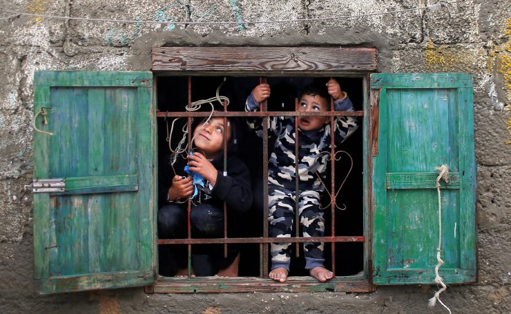 Palestinian children look out of their family's home window on a rainy day at Deir al-Balah refugee camp in the central Gaza Strip December 17, 2020. Reuters