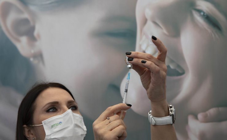 An Israeli nurse prepares a COVID-19 vaccine at a temporary vaccination center in the lobby of a gymnasium in Tel Aviv, Israel, Monday, Dec. 21, 2020. AP