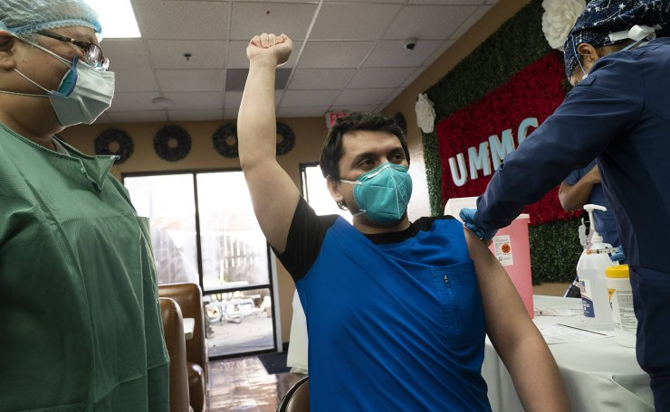 Medical staff member Gabriel Cervera Rodriguez (C) raises his fist to celebrate after receiving the Moderna COVID-19 vaccine at the United Memorial Medical Center on December 21, 2020 in Houston, Texas. Vaccinations in the U.S. began last week with healthcare workers, with at least 556,000 doses reportedly administered. AFP