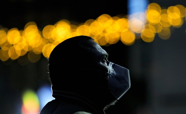 A man wearing a mask against the coronavirus, looks at a screen before the arrival of the first batch of COVID-19 vaccines at the National Center for Storage of the COVID-19 Vaccine, a military run facility, in Bucharest, Romania, Saturday, Dec. 26, 2020. Romanian authorities will start COVID-19 vaccinations on Sunday. AP