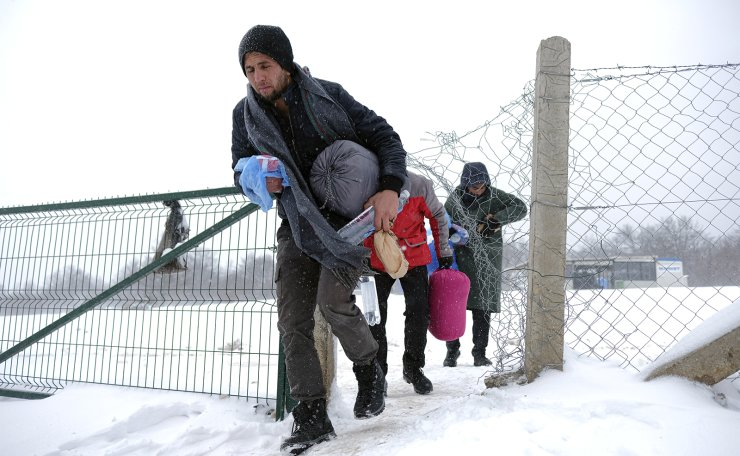 Migrants walk through the snow at the Lipa camp northwestern Bosnia, near the border with Croatia, Saturday, Dec. 26, 2020. Hundreds of migrants are stranded in a burnt-out squalid camp in Bosnia as heavy snow fell in the country and temperatures dropped during a winter spell of bad weather after fire earlier this week destroyed much of the camp near the town of Bihac that already was harshly criticized by international officials and aid groups as inadequate for housing refugees and migrants. AP