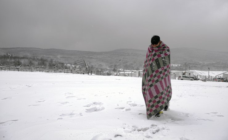 A migrant walks through the snow wrapped in a blanket at the Lipa camp northwestern Bosnia, near the border with Croatia, Saturday, Dec. 26, 2020. AP