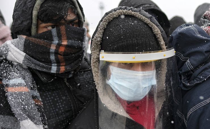 Migrants, one wearing protective equipment against the new coronavirus, wait to be relocated during a snowfall at the Lipa camp northwestern Bosnia, near the border with Croatia, Saturday, Dec. 26, 2020. AP