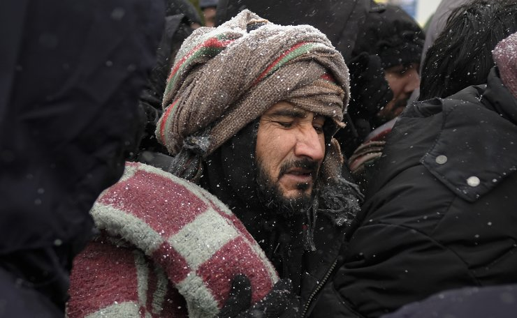 A migrant grimaces as he stands in a crowd waiting to be relocated during a snowfall at the Lipa camp northwestern Bosnia, near the border with Croatia, Saturday, Dec. 26, 2020. AP