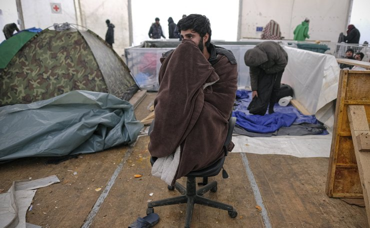 A migrant sits on a chair covered in a blanket in a temporary shelter at the Lipa camp northwestern Bosnia, near the border with Croatia, Saturday, Dec. 26, 2020. AP