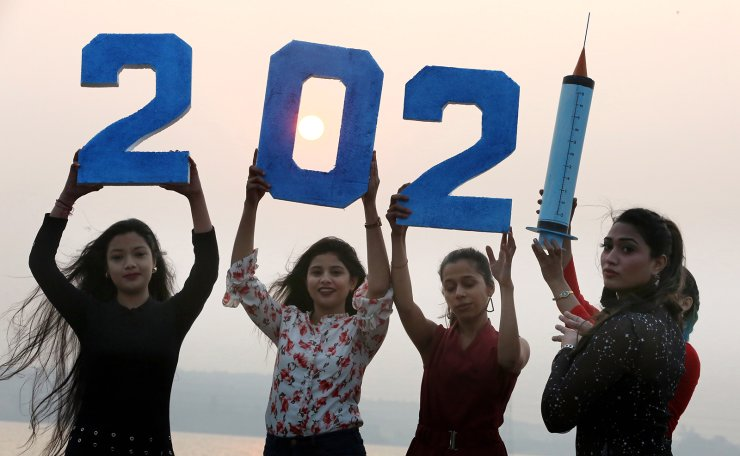 Indian girls hold cutouts of digits and a syringe as they pose for a photograph while celebrating the upcoming new year in Bhopal, India, 30 December 2020. EPA