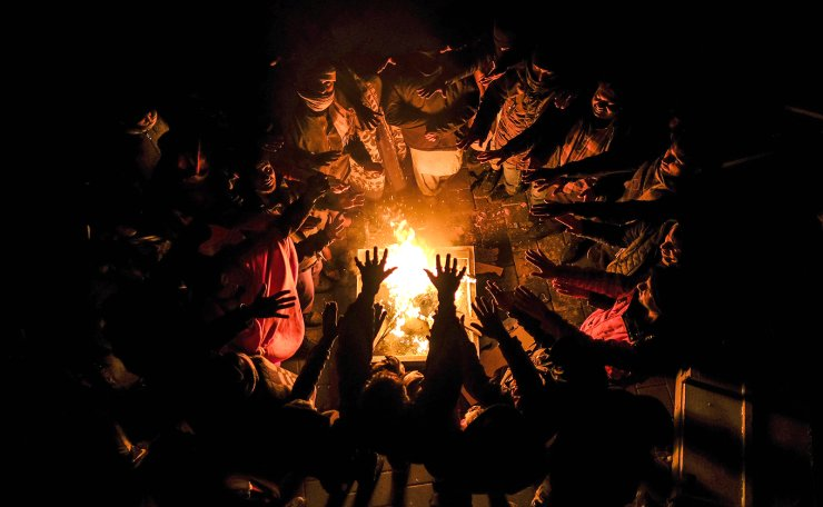 Migrants stretch their hands above a fire at the Lipa camp outside Bihac, Bosnia, Wednesday, Dec. 30, 2020, after hundreds failed to be relocated from the burnt-out tent camp in the northwest of the country. The migrants were supposed on Tuesday to be transferred from the much-criticized Lipa camp to a new location in the central part of the country, but have instead spent some 24 hours in buses before being told on Wednesday afternoon to disembark and return to the now empty camp site. AP