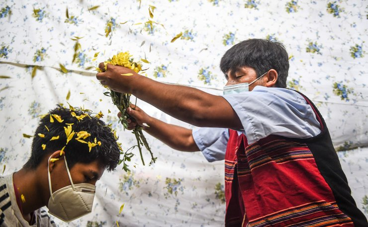 A shaman performs a flower ritual to a man during a ritual of predictions at the Wishes Market in Lima, on December 30, 2020. - Every year before New Year, shamans from the Andean region make predictions for the next year at this market in the Peruvian capital. AFP
