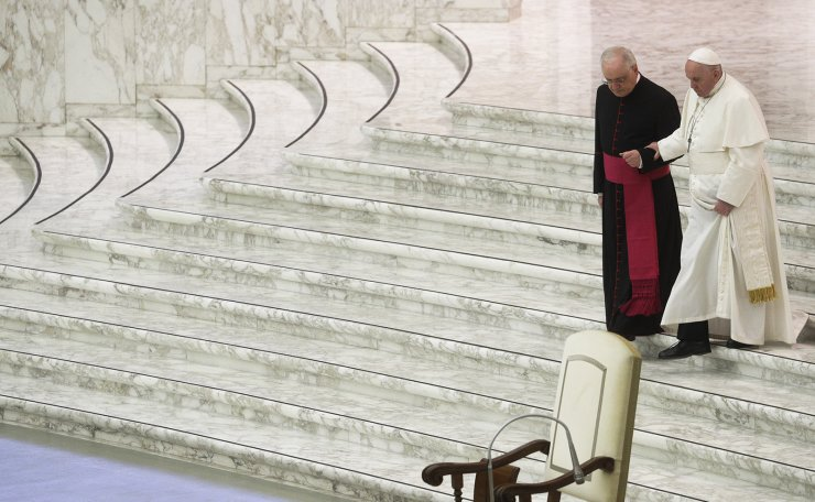 In this Dec. 21, 2020 file photo, Pope Francis is helped by Monsignor Leoardo Sapienza as he walks down the steps to exchange holidays greeting with Vatican employees in the Paul VI hall at the Vatican. Pope Francis is skipping New Year's ceremonies due to what the Vatican says is a painful back condition, the Vatican said Thursday, Dec. 31, 2020. AP