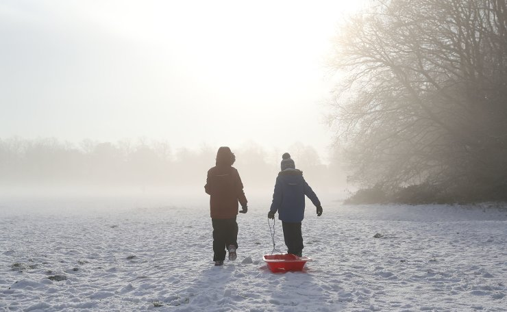 Two children drag a sledge across Knutsford Heath in north east England, Thursday Dec. 31, 2020, after overnight temperatures dropped below freezing. EPA