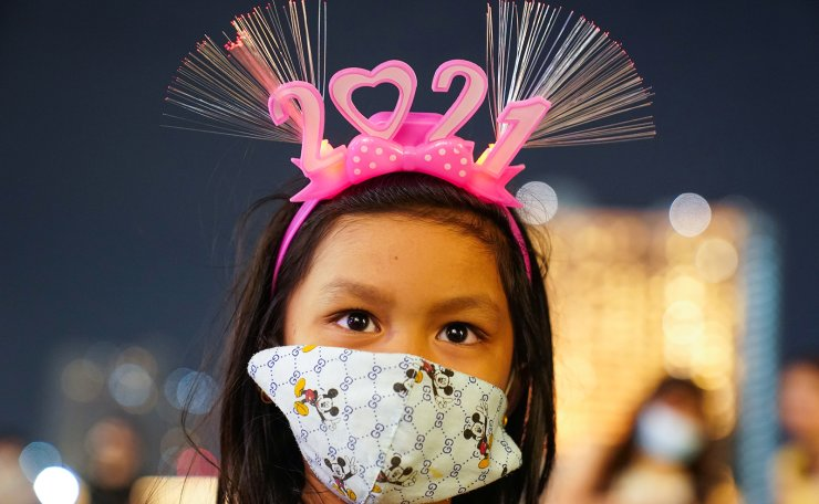 A girl wearing a mask and '2021' head band looks on at a shopping mall as The New Year countdown celebrations and crowded events were banned amid the spread of the coronavirus disease (COVID-19) in Bangkok, Thailand, December 31, 2020. Reuters