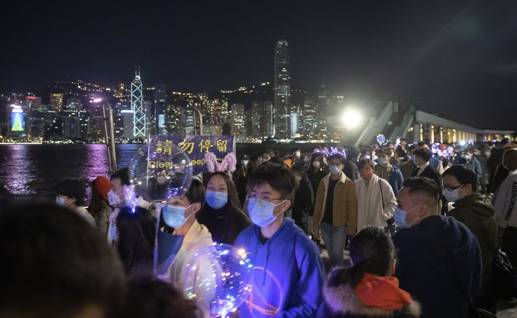 People walk at the waterfront of the Victoria Harbor to celebrate the New Year's Eve ahead of the year 2021, in Hong Kong, Thursday, Dec. 31, 2020. AP