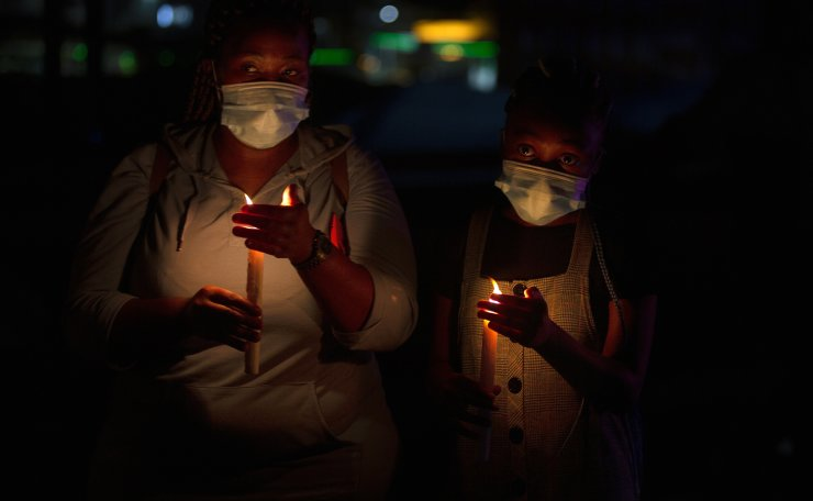 Frontline workers attend a candlelight ceremony on New Year's Eve on the famed Nelson Mandela Bridge in downtown Johannesburg Thursday, Dec. 31, 2020. Many South Africans will swap firecrackers for candles to mark New Year's Eve amid COVID-19 restrictions including a nighttime curfew responding to President Cyril Ramaphosa's call to light a candle to honor those who have died in the COVID-19 pandemic and the health workers who are on the frontline of battling the disease. AP