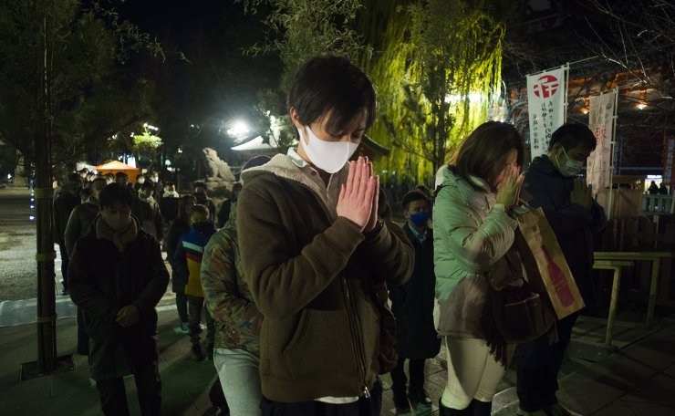 People pray at Asakusa Shrine on New Year's Day in Tokyo early Friday, Jan. 1, 2021. AP