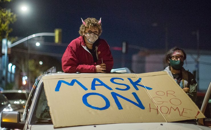 In this file photo taken on December 30, 2020 protesters wearing face masks stand on their vehicle as they participate along with homeless advocates in a protest against Christian musician Sean Feucht as he plans to hold a public event in Skid Row in spite of the rise of Covid-19 cases in the region, in Los Angeles. AFP