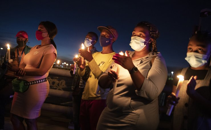 Members of the public stand with candles during a memorial for victims of the Covid-19 Coronavirus on New Year's eve who have died in the city during 2020, Johannesburg, South Africa, 31 December 2020. EPA