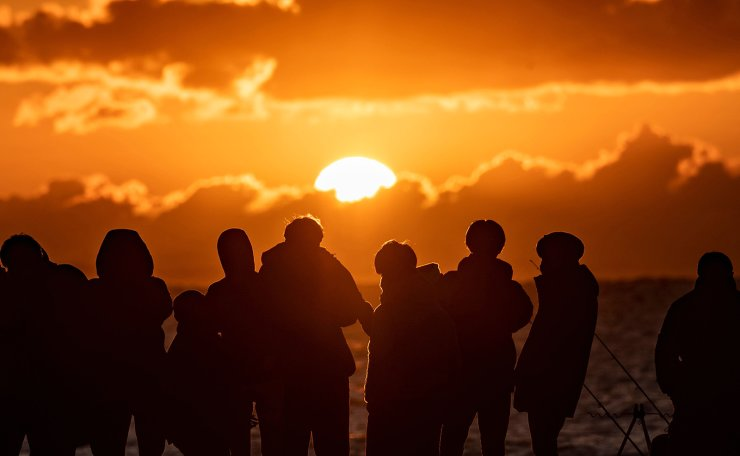 People gather at Southern Beach of Chigasaki to watch the sunrise on New Year's Day in Kanagawa Prefecture, southwest of Tokyo on January 1, 2021. AFP