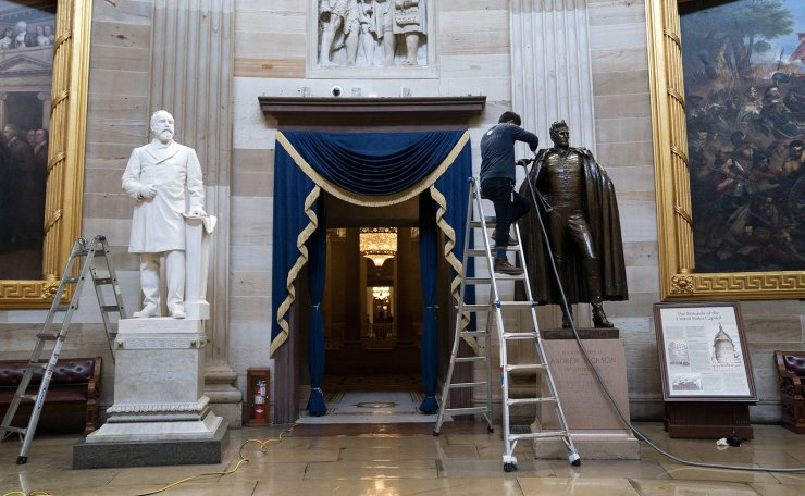 A worker cleans the statue of former President Andrew Jackson in the rotunda of the U.S. Capitol on January 12, 2021 in Washington, DC. AFP