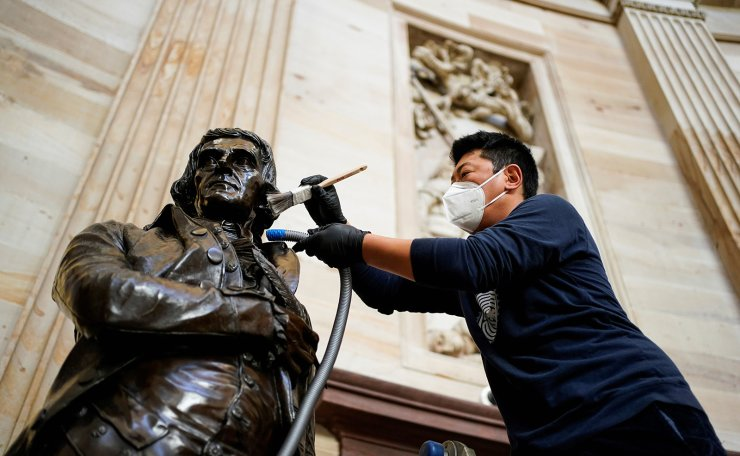 Gompo Yarmolinsky with the Architect of the Capitol cleans dust from the statue of Thomas Jefferson in the Capitol Rotunda after supporters of U.S. President Donald Trump stormed the U.S. Capitol in Washington, U.S., January 12, 2021. Reuters