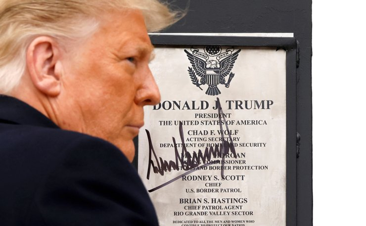 U.S. President Donald Trump signs a plaque placed at the U.S.-Mexico border wall during his visit, in Alamo, Texas, U.S., January 12, 2021. Reuters
