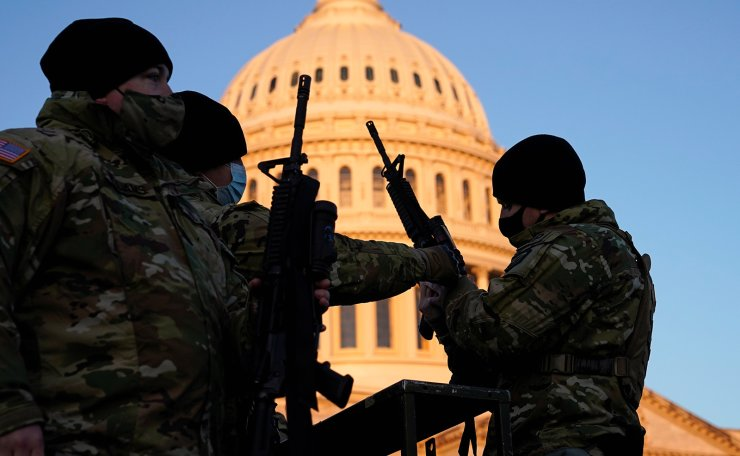 Members of the National Guard are given weapons before Democrats begin debating one article of impeachment against U.S. President Donald Trump at the U.S. Capitol, in Washington, U.S., January 13, 2021. Reuters