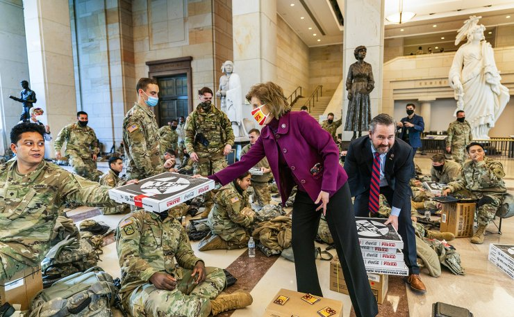 Rep. Vicky Hartzler, R-Mo., and Rep. Michael Waltz, R-Fla., hand pizzas to members of the National Guard gathered at the Capitol Visitor Center, Wednesday, Jan. 13, 2021, in Washington. as the House of Representatives continues with its fast-moving House vote to impeach President Donald Trump, a week after a mob of Trump supporters stormed the U.S. Capitol. AP