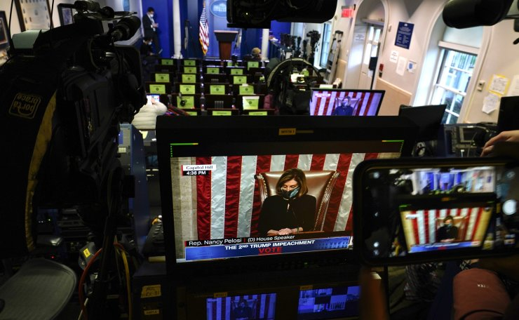 A person photographs network monitors inside the White House briefing room that display the impeachment proceedings going at the U.S. Capitol against President Donald Trump, Tuesday, Jan. 12, 2021 in Washington. AP