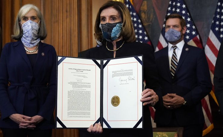 House Speaker Nancy Pelosi of Calif., displays the signed article of impeachment against President Donald Trump in an engrossment ceremony before transmission to the Senate for trial on Capitol Hill, in Washington, Wednesday, Jan. 13, 2021. AP