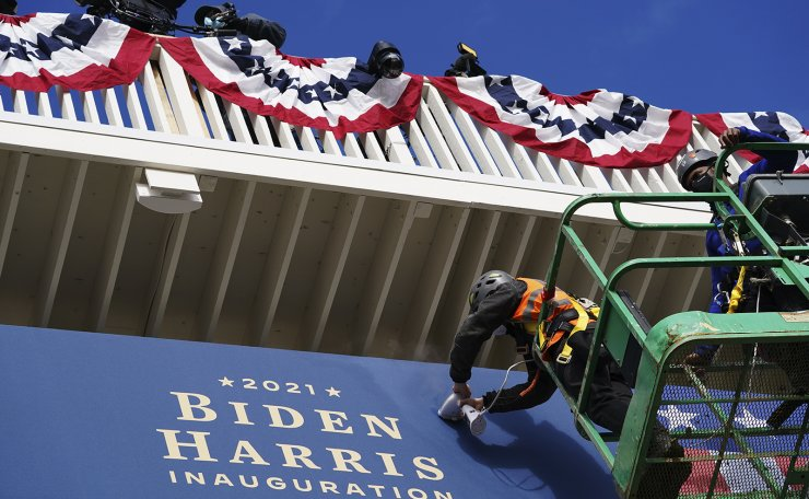 Workers install bunting outside the White House as preparations are made for President-elect Joe Biden's inauguration ceremony, Monday, Jan. 18, 2021, in Washington. AP
