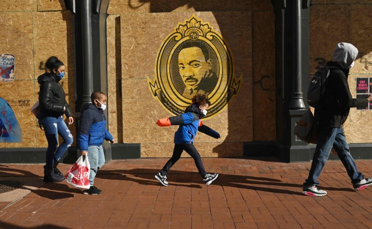 People walk by a boarded up building with a poster of US civil rights leader Martin Luther King Jr. on a holiday observed in his name in Washington, DC on January 18, 2021, ahead of the inauguration of US President-elect Joe Biden as the next US president.  AFP