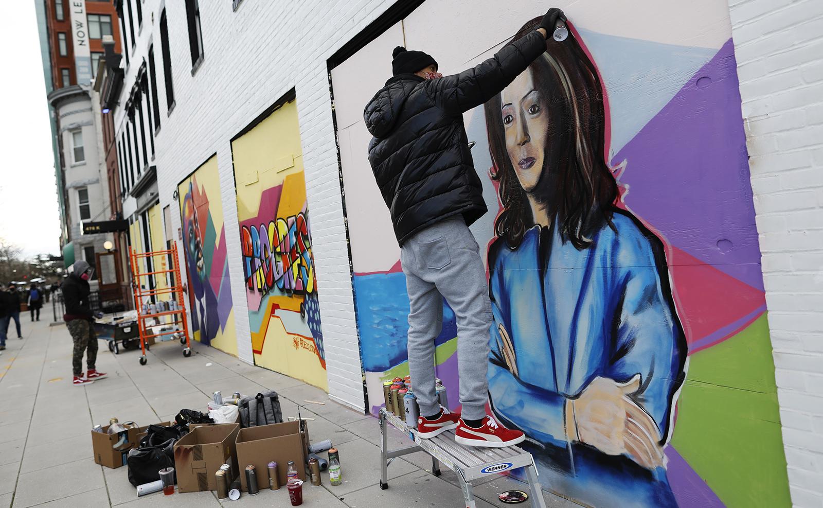 Shawn Perkins spray paints a mural of Vice President-elect Kamala Harris ahead of President-elect Joe Biden's inauguration ceremony, Monday, Jan. 18, 2021, in Washington. AP