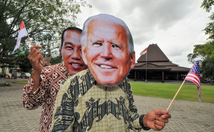 People wearing masks depicting the faces of Indonesian President Joko Widodo (L) and US President-elect Joe Biden (R) pose in Surakarta, Central Java on January 20, 2020, ahead of Biden's presidential inauguration later in the day. AFP