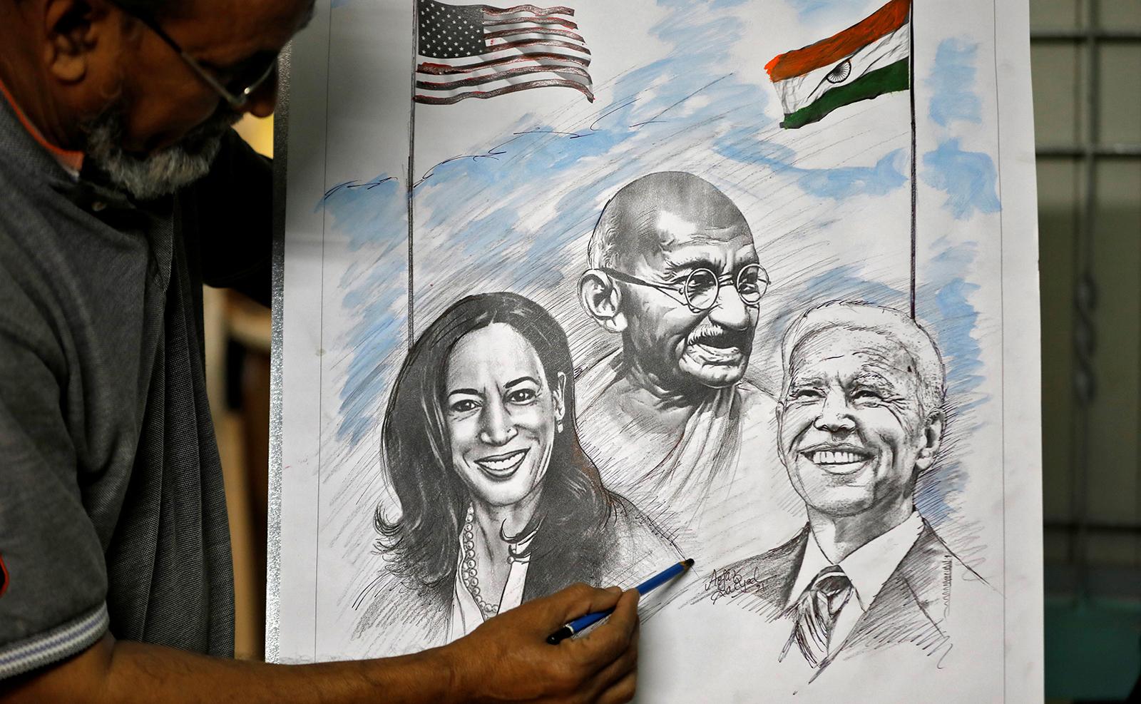Aejaz Saiyad, an artist, gives finishing touches to a drawing of U.S. President-elect Joe Biden, Vice President-elect Kamala Harris and India's independence hero Mahatma Gandhi at his home in Ahmedabad, India, January 20, 2021. REUTERS