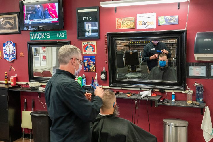 The family of President-elect Joe Biden is seen on a television screen as they arrive for the 59th Presidential Inauguration at the U.S. Capitol in Washington as barber Mark Mackrell gives a haircut to a regular at Mackell's Barber Shop, Wednesday, Jan. 20, 2021, in downtown Scranton, Pa. AP