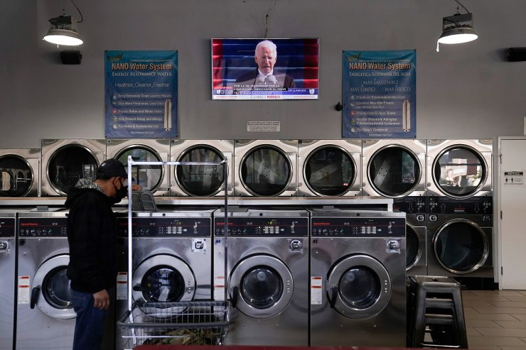 A Hispanic man checks on his laundry as a live broadcast of President Joe Biden's speech is shown on a TV Wednesday, Jan. 20, 2021, in Los Angeles. AP