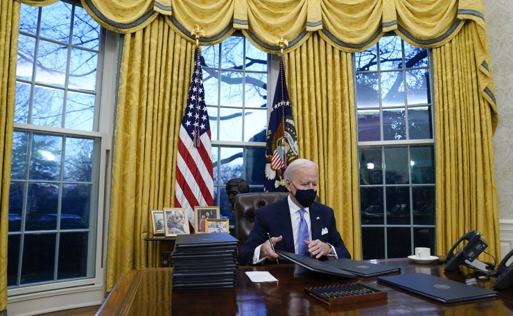 President Joe Biden signs his first executive orders in the Oval Office of the White House on Wednesday, Jan. 20, 2021, in Washington. AP