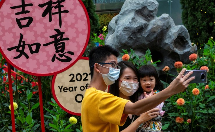 Visitors pose for a wefie during the annual Dahlia Dreams floral display ahead of the Chinese Lunar New Year of the Ox, otherwise known as the Spring Festival, at Singapore's Gardens by the Bay, January 31, 2021. REUTERS