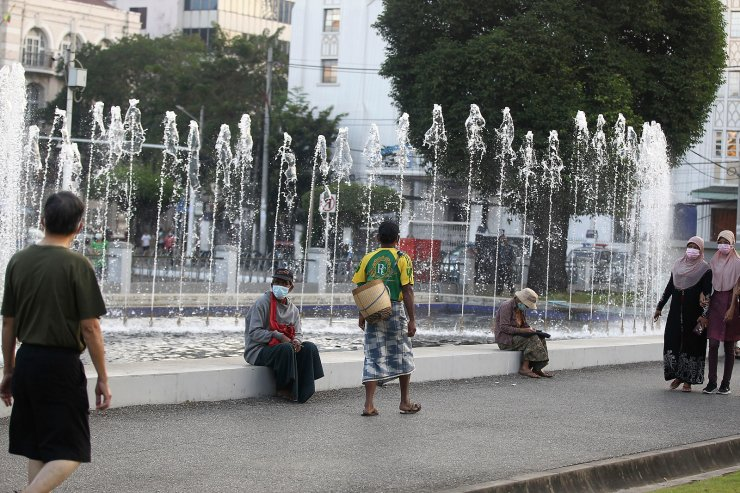 People walk next to a water fountain Monday, Feb. 1, 2021 in Yangon, Myanmar. AP