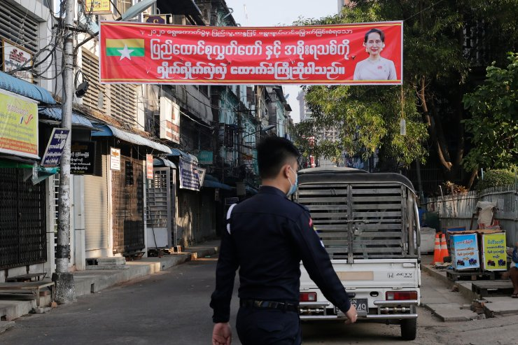A man walks pass near a poster reading 'We Welcome the Assembly of the Union (national-level bicameral legislature of Myanmar) and new government' displayed at a street at downtown area in Yangon, Myanmar, 01 February 2021. EPA
