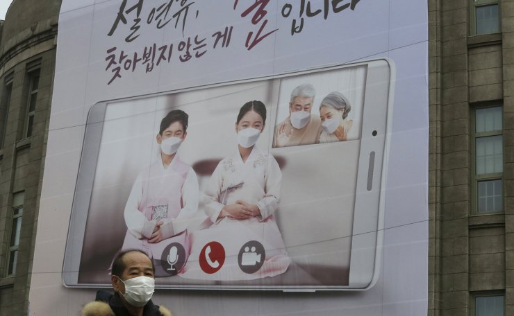 A man wearing a face mask as a precaution against the coronavirus passes by a banner calling on residents to refrain from visiting families and relatives during the upcoming Lunar New Year holidays that start Feb. 11, in front of Seoul City Hall in Seoul, South Korea, Monday, Feb. 1, 2021. South Korea on Sunday said it will maintain elevated social distancing measures for at least two more weeks as health officials raise concerns about a possible surge in coronavirus infections surrounding the Lunar New Year holidays. The banner reads: 'It is a filial piety not to visit during the Lunar New Year holidays.' AP