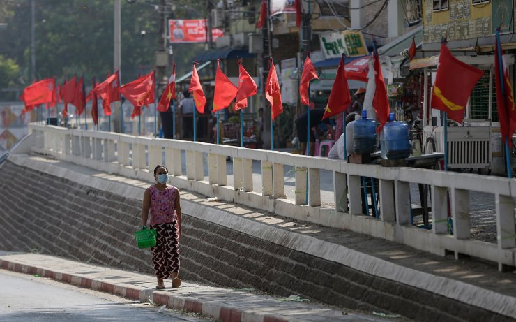 A woman walks near the flags of the National League for Democracy party, chaired by Aung San Suu Kyi, decorated along a main road in Yangon, Myanmar, 01 February 2021. AFP