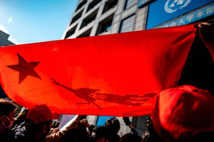 Myanmar activists chant slogans and hold a National League for Democracy flag during a protest outside the United Nations University building in Tokyo on February 1, 2021, after Myanmar's military seized power in a bloodless coup and detaining democratically elected leader Aung San Suu Kyi as it imposed a one-year state of emergency. AFP