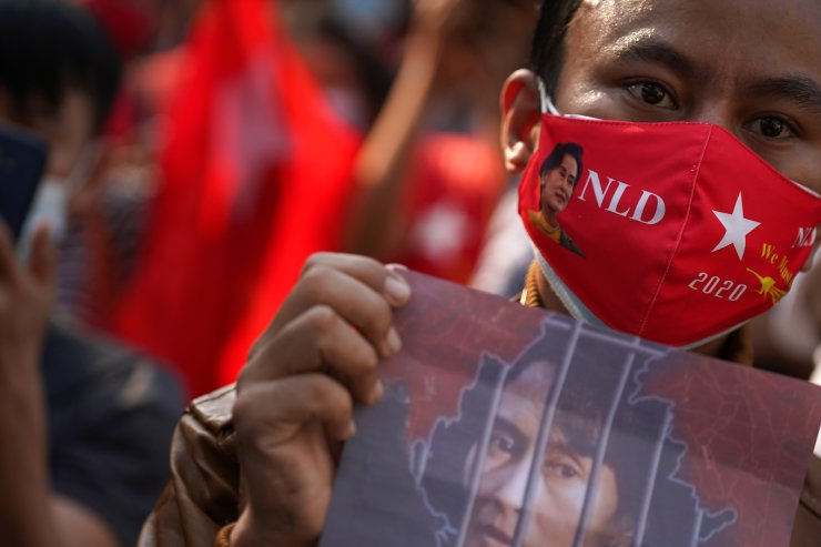 Supporter wearing an NLD party-themed mask holds a picture of leader Aung San Suu Kyi in front of Myanmar's embassy during a rally after the military seized power from a democratically elected civilian government and arrested Aung San Suu Kyi, in Bangkok, Thailand February 1, 2021. REUTERS