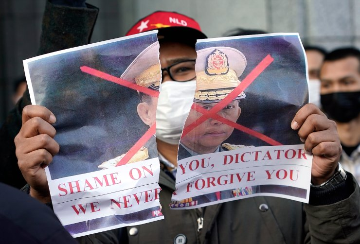 A member of Myanmar community in Japan holds up a torn picture of Myanmar's military chief Min Aung Hlaing during a protest held in front of the United Nations University in Tokyo, Japan, 01 February 2021. EPA