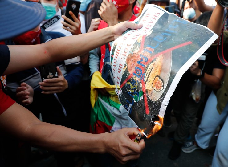 Burmese living in Thailand set a fire on a picture of Myanmar military Commander-in-Chief Senior Gen. Min Aung Hlaing during a protest in front of the Myanmar Embassy, in Bangkok, Thailand, Monday, Feb. 1, 2021. AP