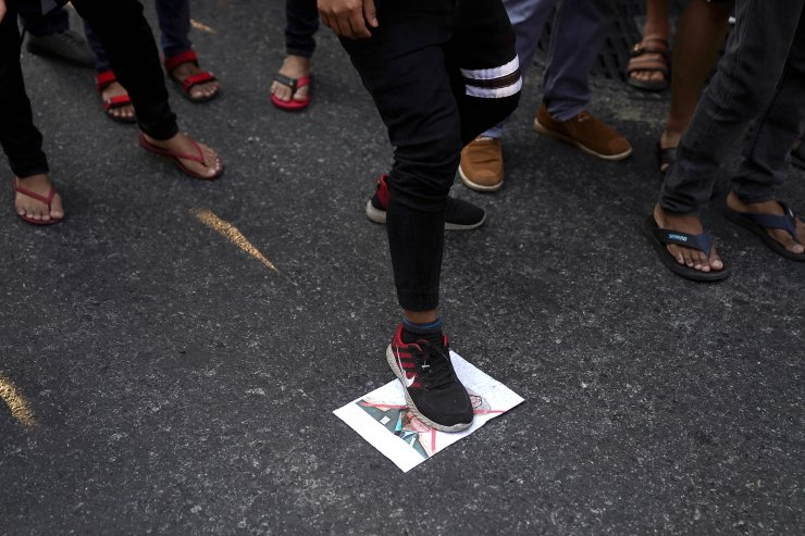 Protester steps on a picture of Myanmar's army chief Min Aung Hlaing, outside Myanmar's embassy after the military seized power from a democratically elected civilian government and arrested its leader Aung San Suu Kyi, in Bangkok, Thailand February 1, 2021. REUTERS