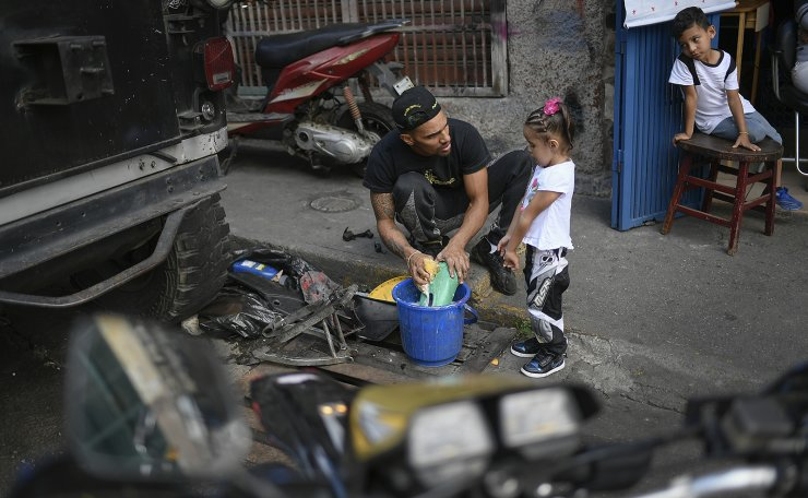Motorcycle stuntman Pedro Aldana cleans motorcycle parts with his daughter Alanis as his young neighbor and admirer, 6-year-old Milan Sandoval Ramos, watches from a chair outside their home in the Catia neighborhood of Caracas, Venezuela, Thursday, Jan. 21, 2021. AP