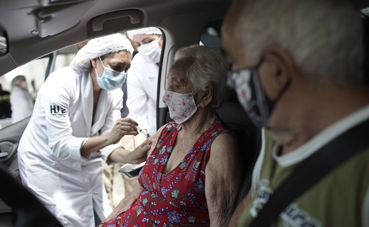 An elderly woman gets a shot of China's Sinovac CoronaVac vaccine as part of a priority COVID-19 vaccination program for the elderly at a drive-thru vaccination center in Rio de Janeiro, Brazil, Monday, Feb. 1, 2021. AP