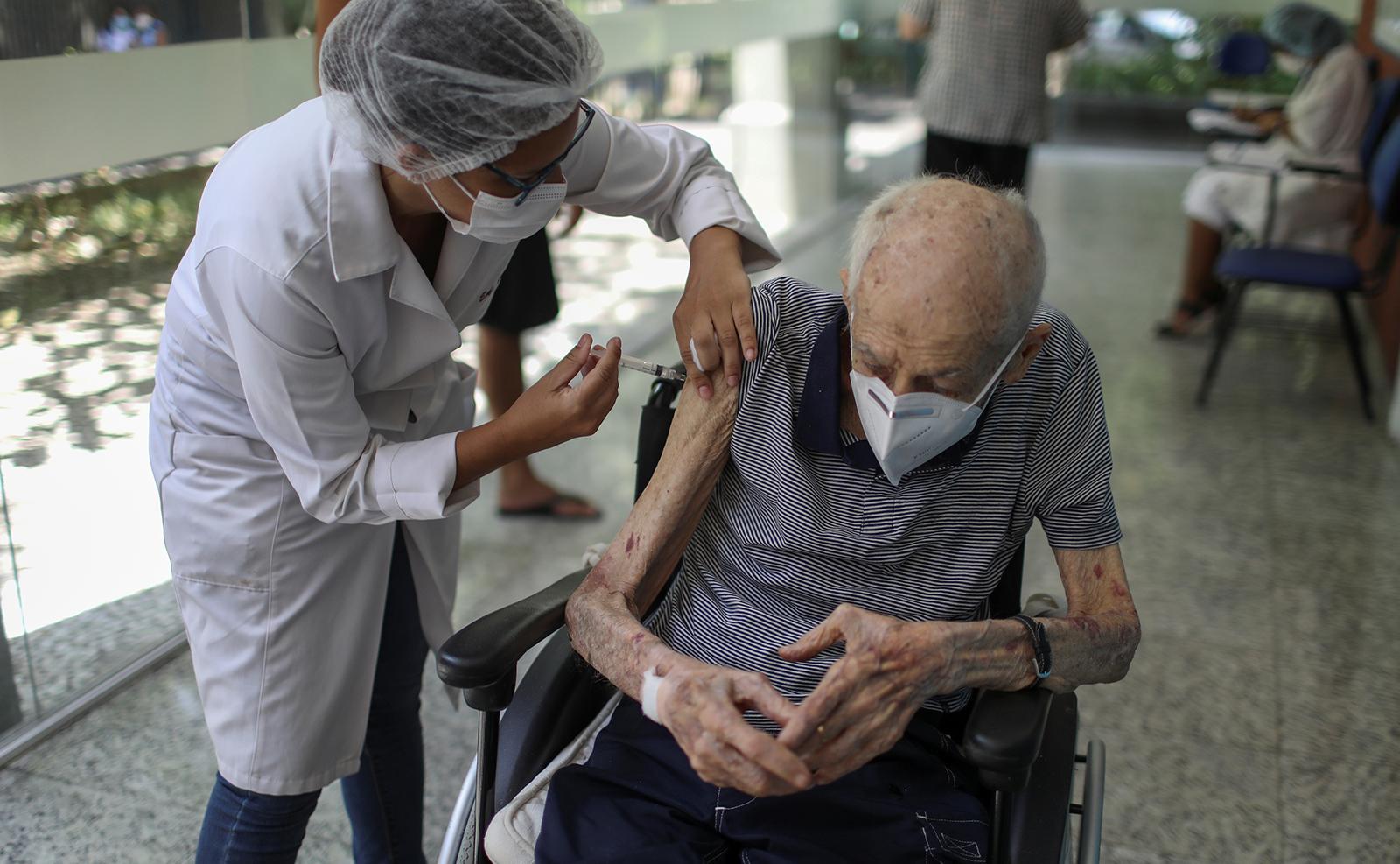 Journalist Helio Fernandes, 100, receives the AstraZeneca/Oxford vaccine for the coronavirus disease (COVID-19) at a public hospital in Rio de Janeiro, Brazil, February 1, 2021. REUTERS